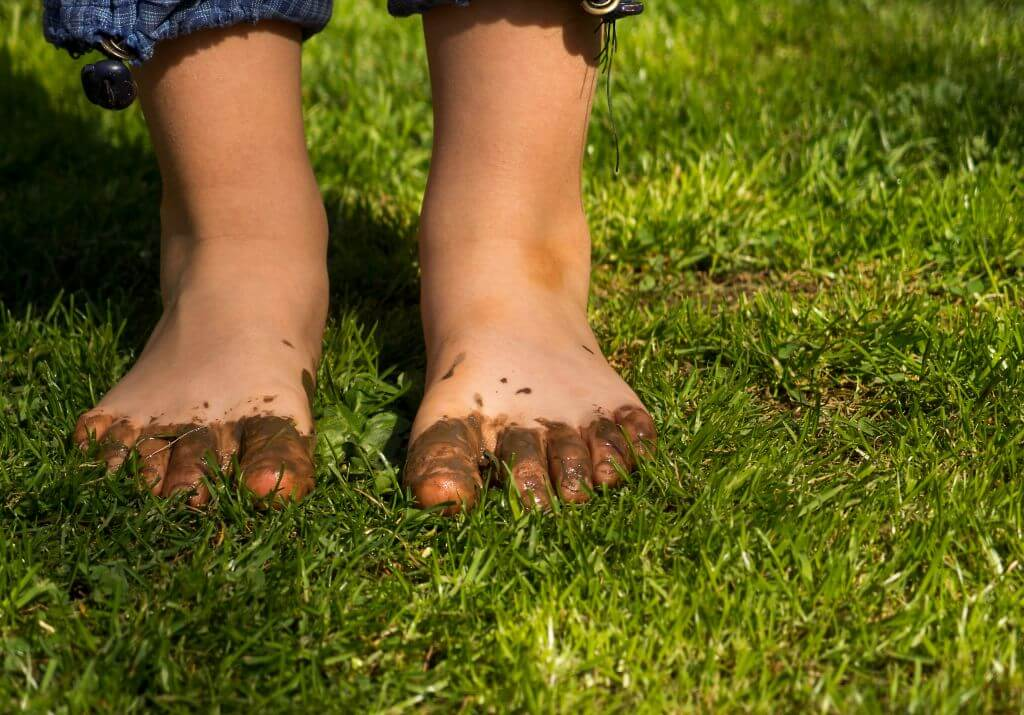 Child's toes in mud and grass
